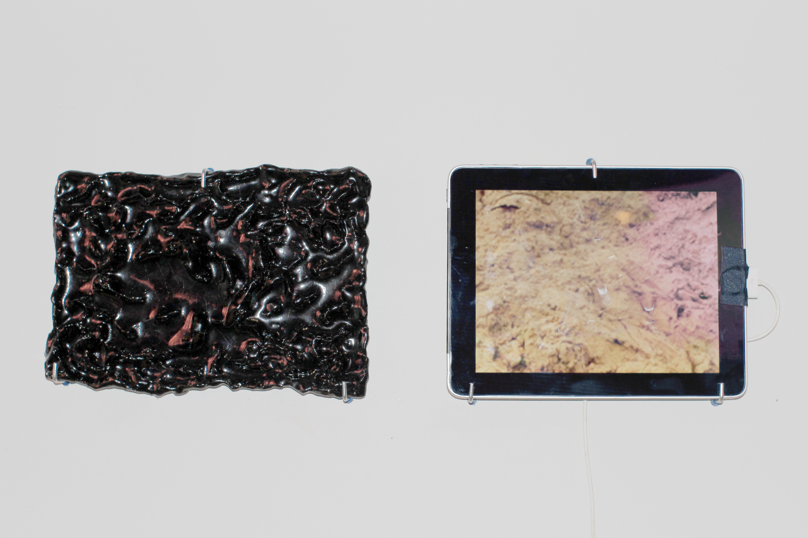 Two Types of Clay, 2017. Installation at Dotory, Brooklyn clay; glass; glaze; iPad with image of coltan mine in Congo (image can be moved and enlarged by hand). An image is the form of a thing.
