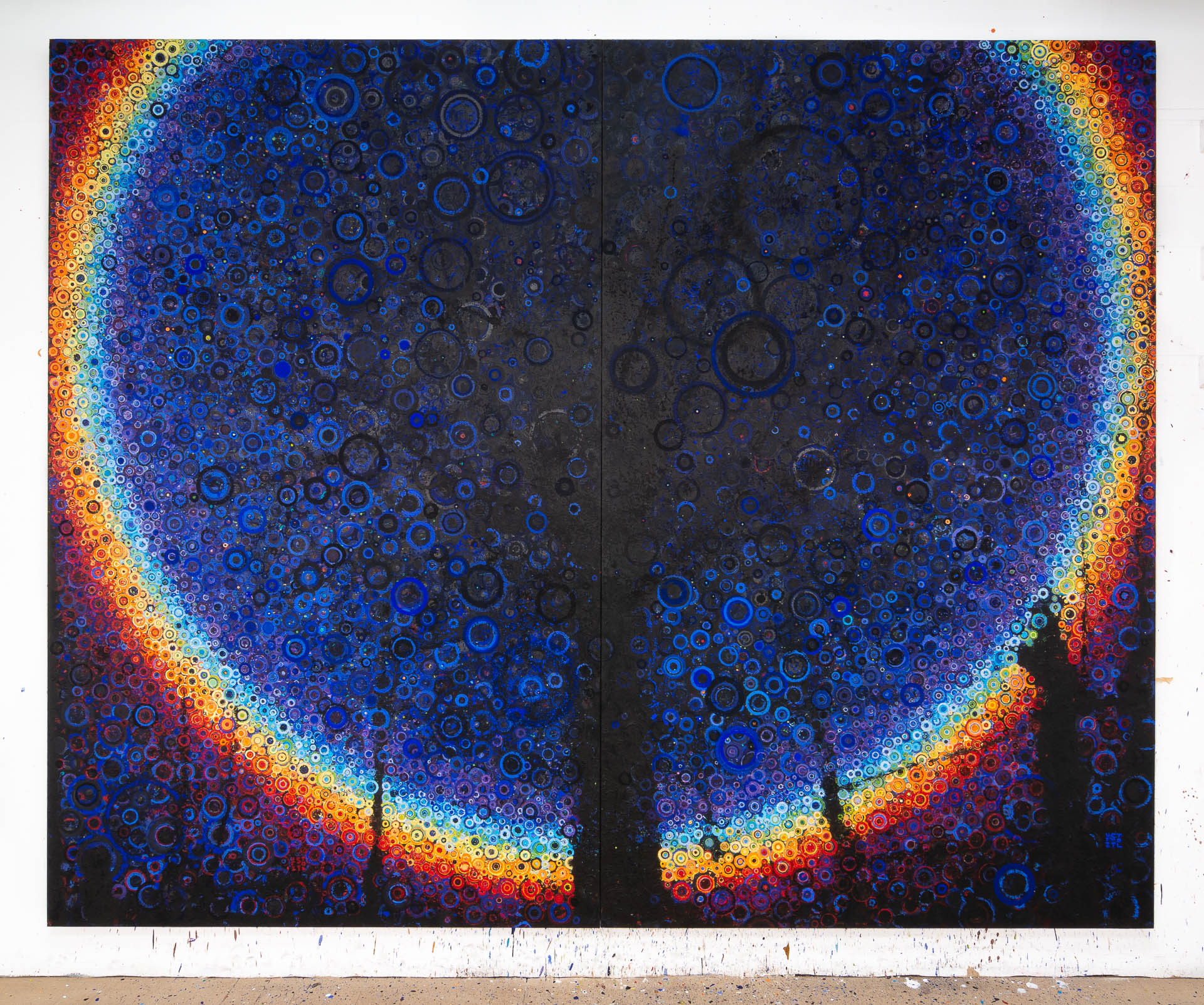 An 8 by 10 foot painting of a dark tree silhouetted against a dark blue background and a large circular rainbow. The image is created across a field of many hand-painted circles