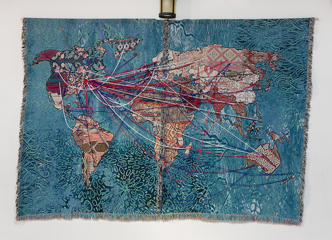 Detailed fiber tapestry of the earth with strands of fabric connecting continents