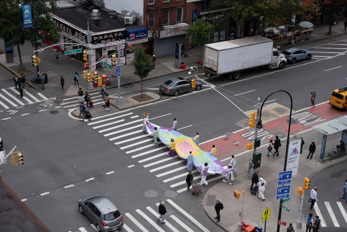 Image looking down on a city intersection with a group of people holding large rainbow fabric in the cross walk